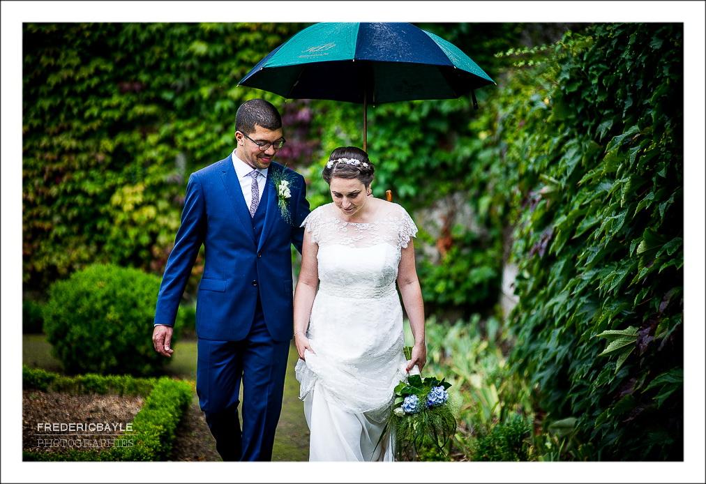 mariés marchant sous la pluie dans un jardin