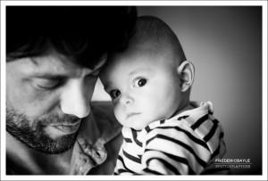 bébé dans les bras de papa fixant le photographe