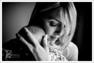 Portrait en noir et blanc d'une maman serrant son bébé contre elle