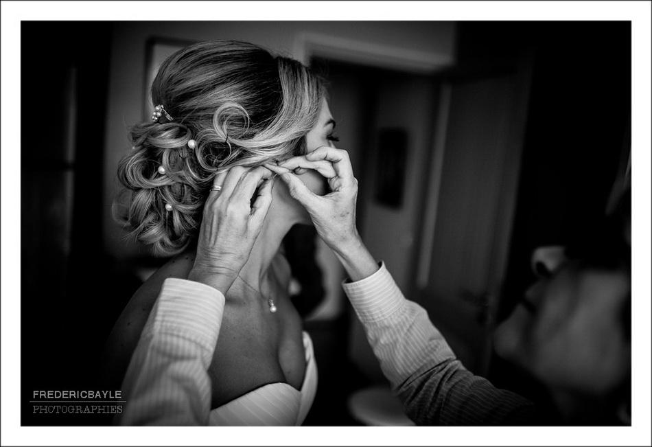 la mariée accroche ses boucles d'oreille