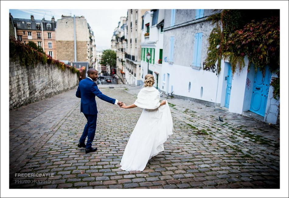 Couple de mariés descendant une rue pavée