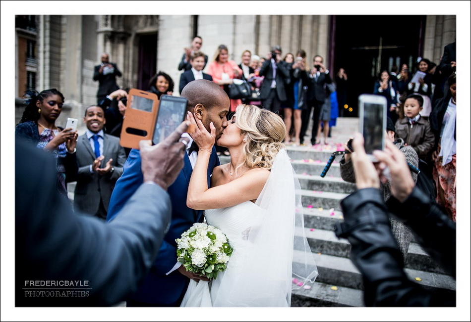 Les mariés s'embrassent devant l'église