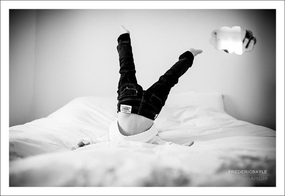petite fille s'amusant sur son lit, photo noir et blanc en mode reportage