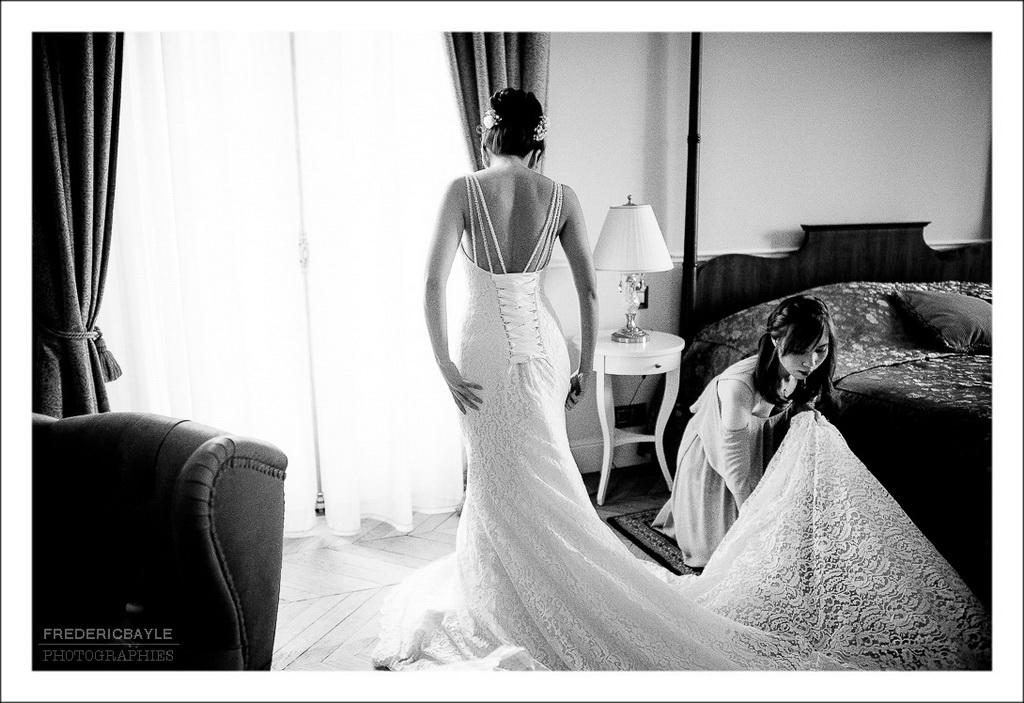 la mariée met sa robe de mariage