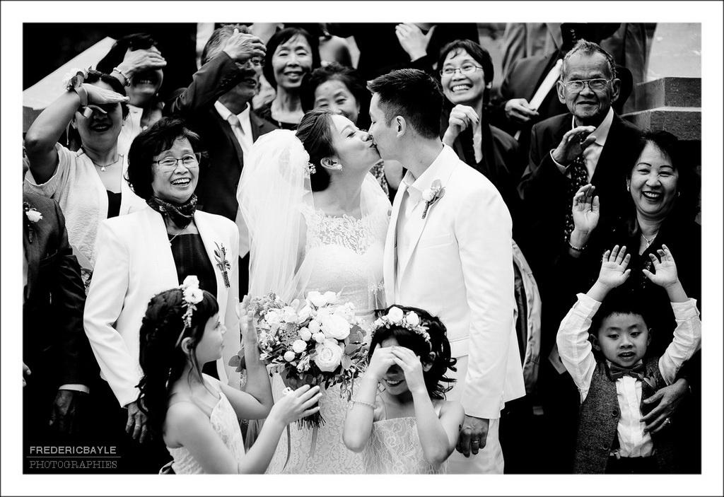 baiser des mariés entourés de leurs familles