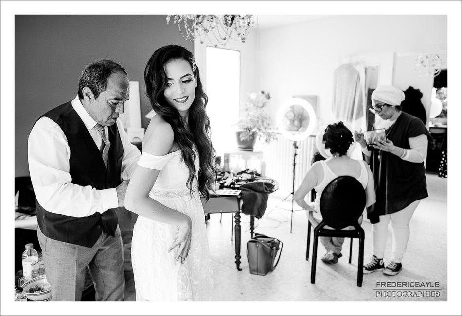 Le papa de l amariée l'aide à attacher sa robe de mariage