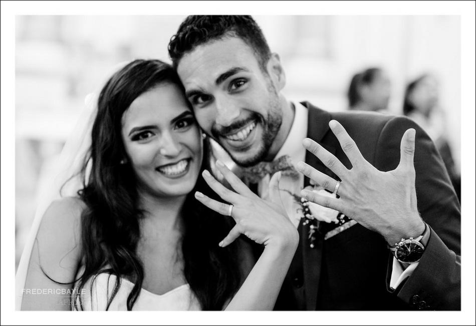 Les mariés montrent leurs alliances au photographe du mariage