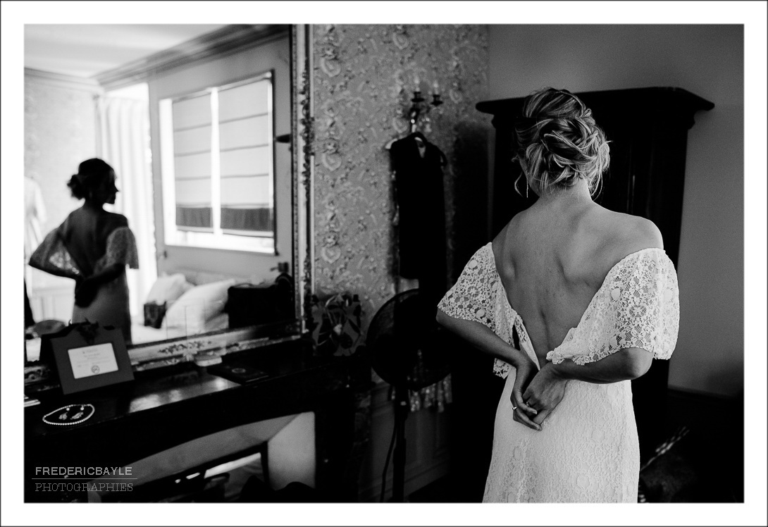 La mariée de dos se regardant dans le miroir avec sa belle robe