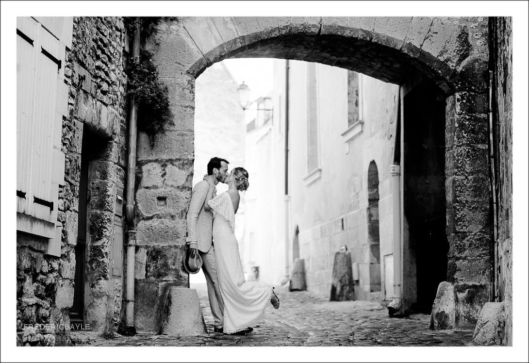 Baiser des mariés de profil sous un porche