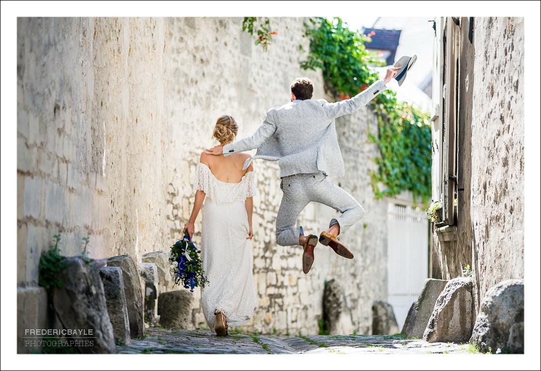 Vue de dos du couple avec le marié qui saute comme un danseur