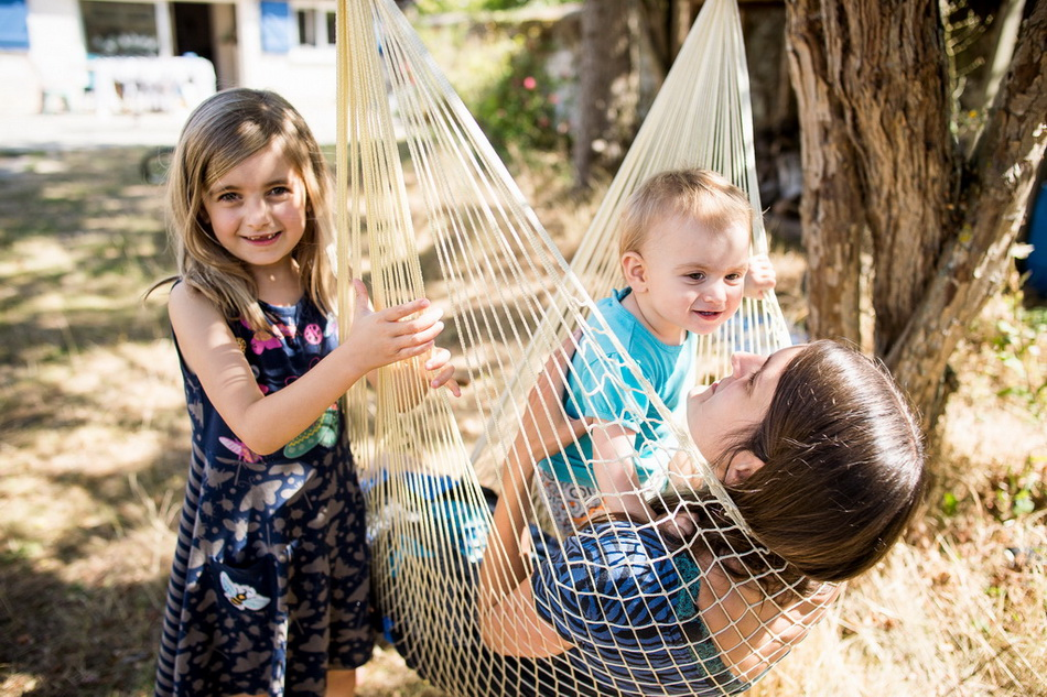 maman et ses deux enfants dans le hamac balançoire du jardin