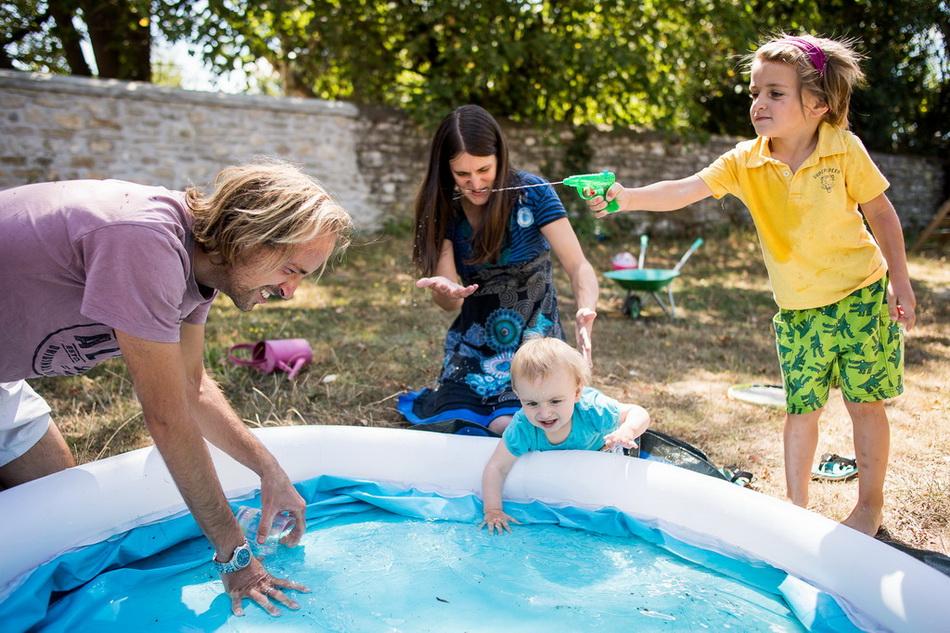 famille jouant dans la piscine à s'éclabousser