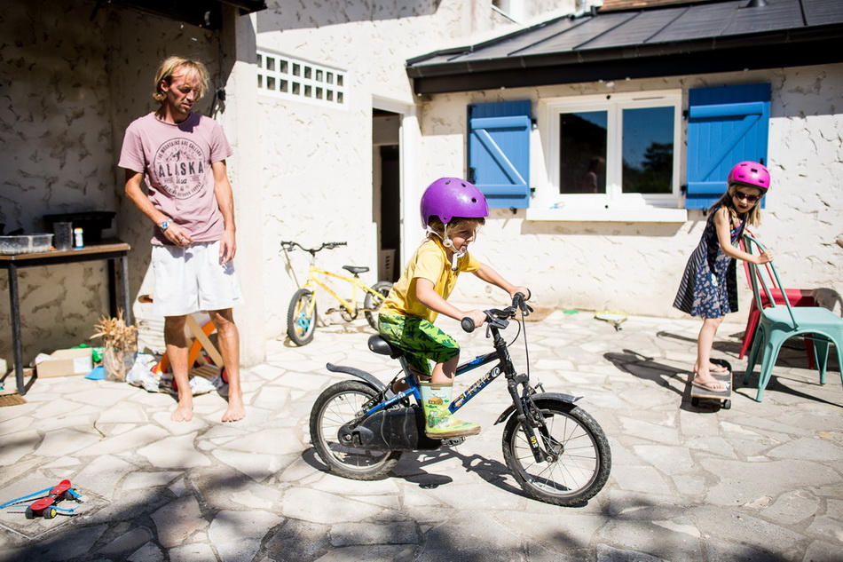 papa et les enfants en train de faire du vélo devant la maison de campagne