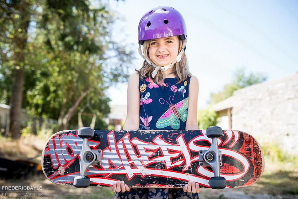 petite fille posant pour le photographe famille avec son skate