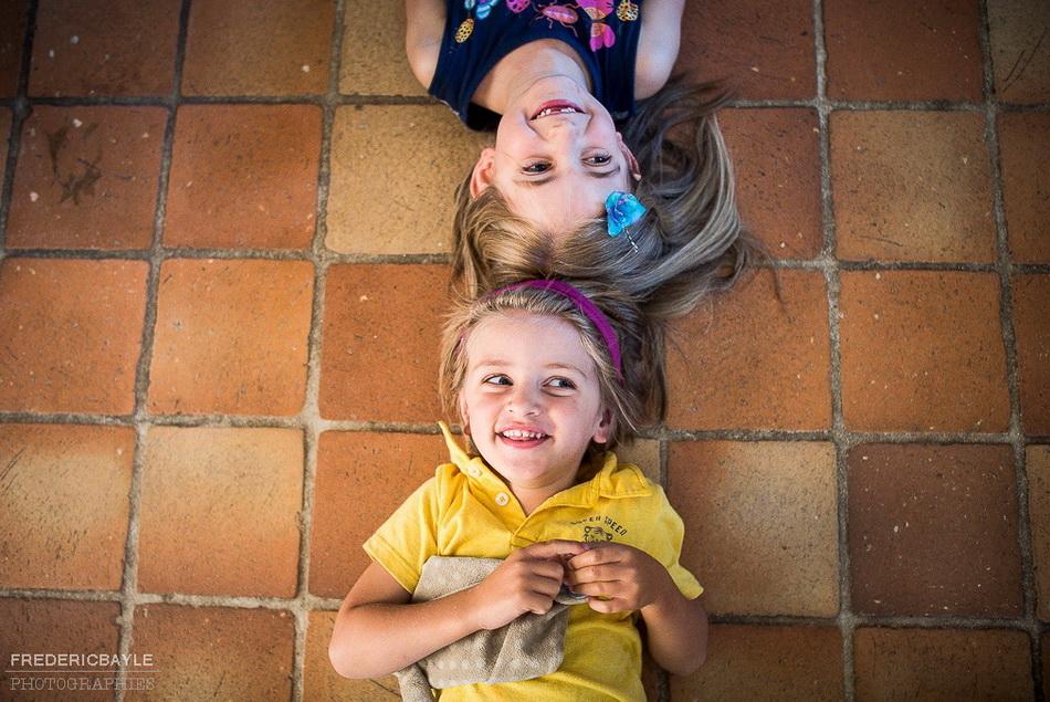 photo de deux enfants jouant dans la maison à poser pour le photographe famille
