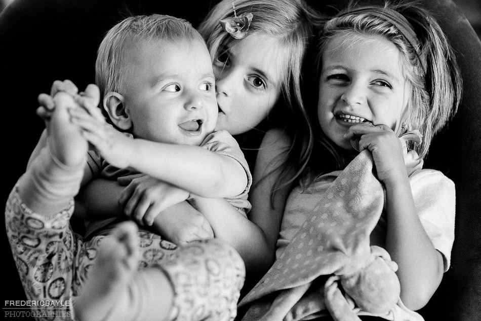 cliché en noir et blanc des trois enfants ensemble posant pour le photographe