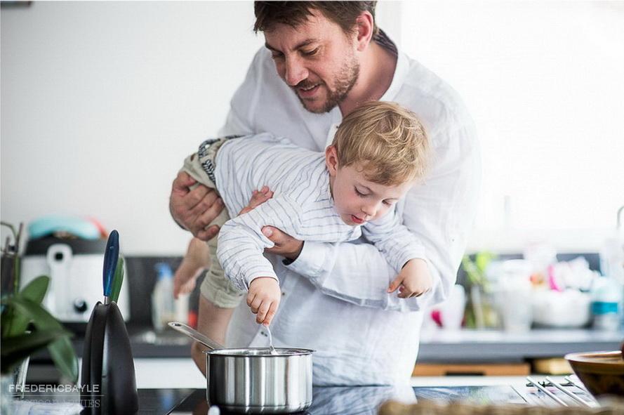papa faisant la cuisine avec bébé durant un reportage famille
