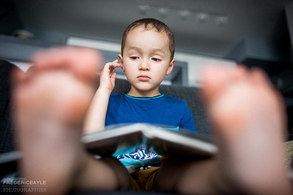 petit garçon lisant un livre sur un reportage famille