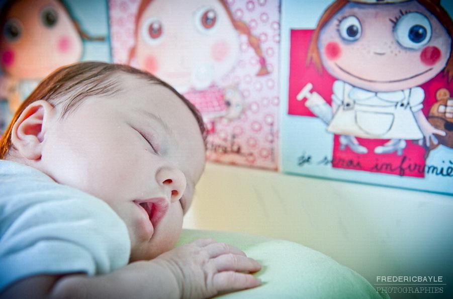 bébé qui dort avec des photos de bébé au second plan