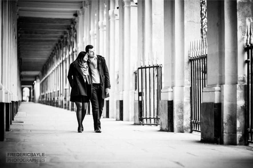 couple enlacé déambulant dans les arcades du Palais Royal à Paris