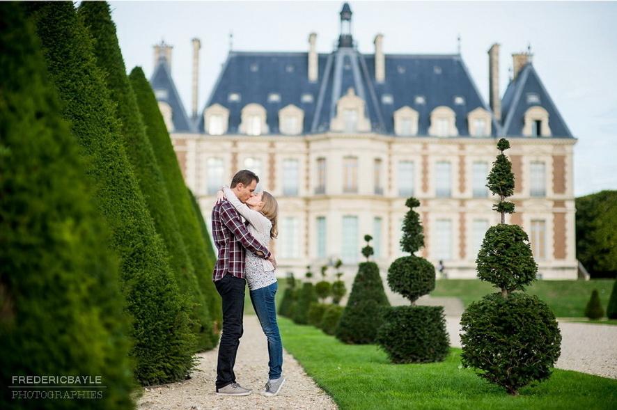 jeune couple s'enlaçant devant le Château de Sceaux