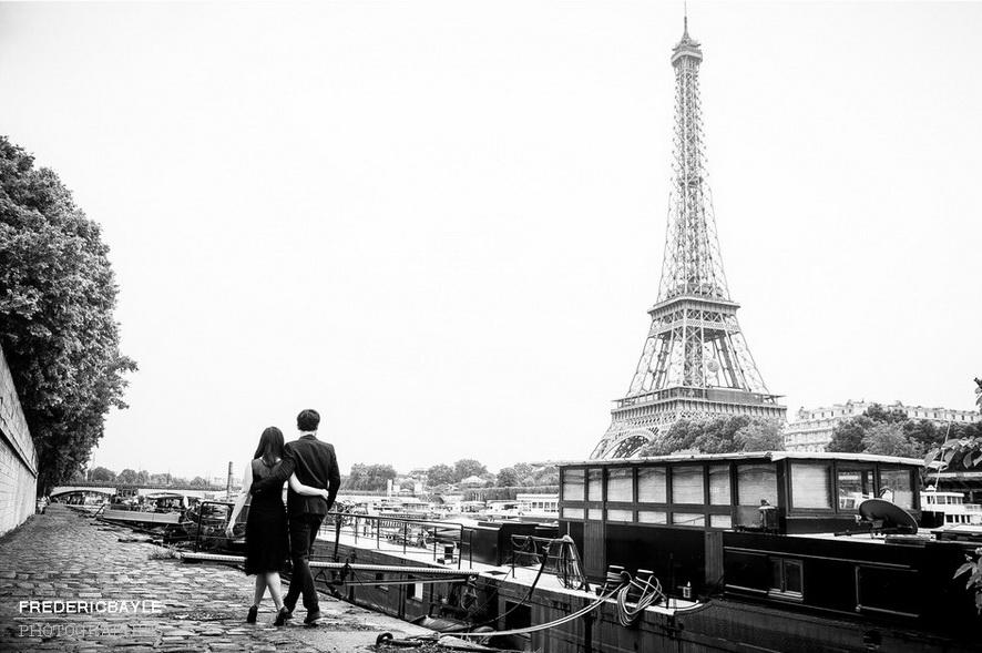 deux jeunes asiatiques enlacés marchant avec la Tour Eiffel en arrière plan
