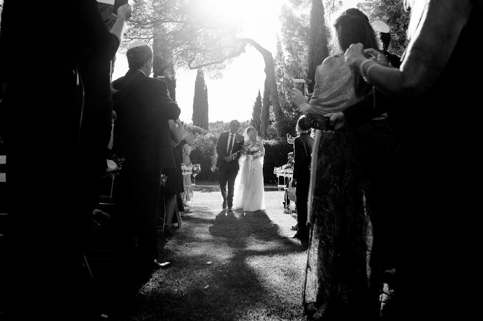 belle photo à contre-jour de la mariée arrivant avec son père