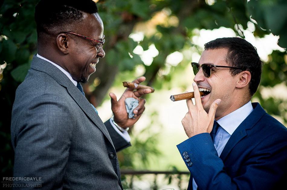 deux invités fument un cigare en rigolant