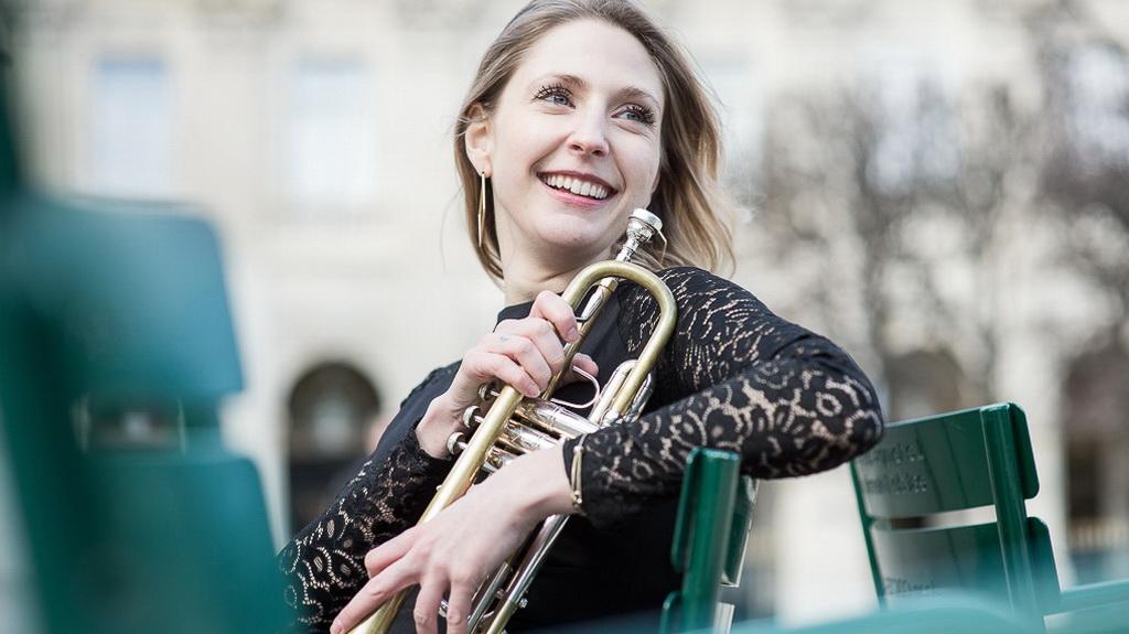 portrait en contre-plongée d'une jeune femme, artiste trompettiste