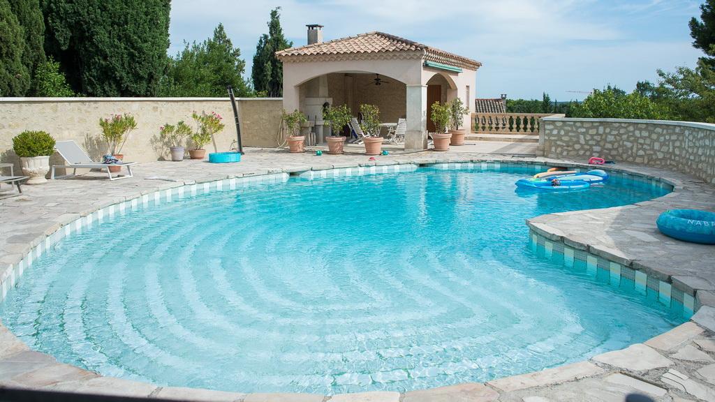 """belle piscine """"haricot"""" sur la terrasse d'une grande maison provençale, dans les Alpilles"""